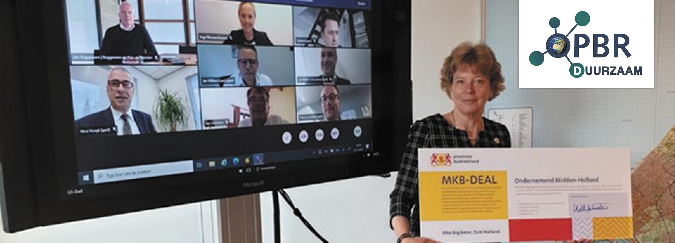 Een vrouw houdt het certificaat van de mkb-deal vast voor een scherm met alle betrokkenen in een videocall.